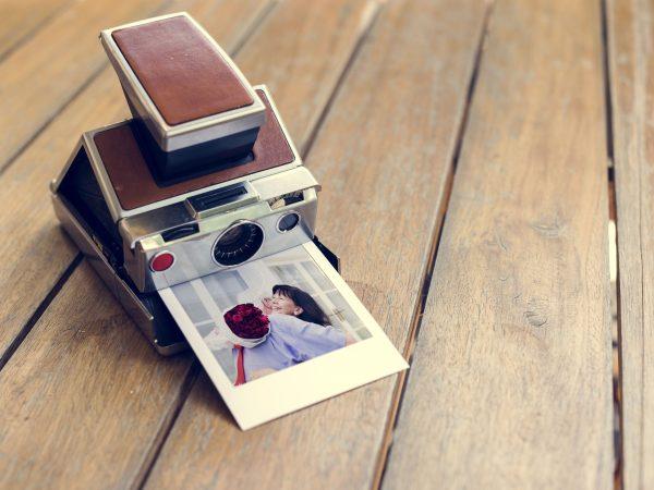 Imagem de câmera instantânea com foto saindo sobre mesa.