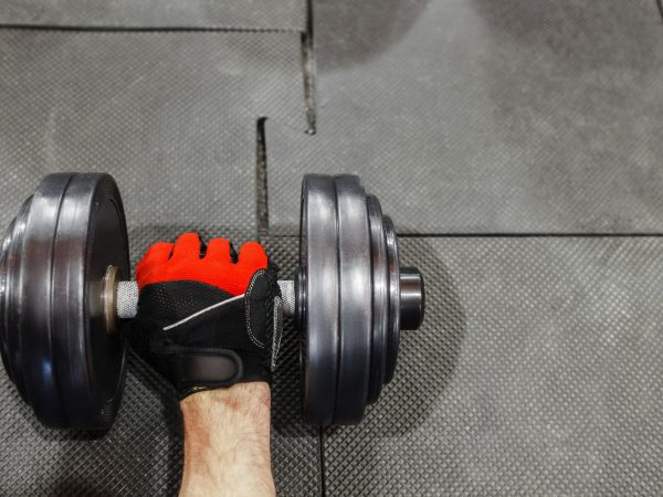 Male hand in sport glove holding dumbbell void. Top voew on dumbbell on gym floor with athlete hand taking it. Professional athlete hand in gloves with dumbbell, copyspace