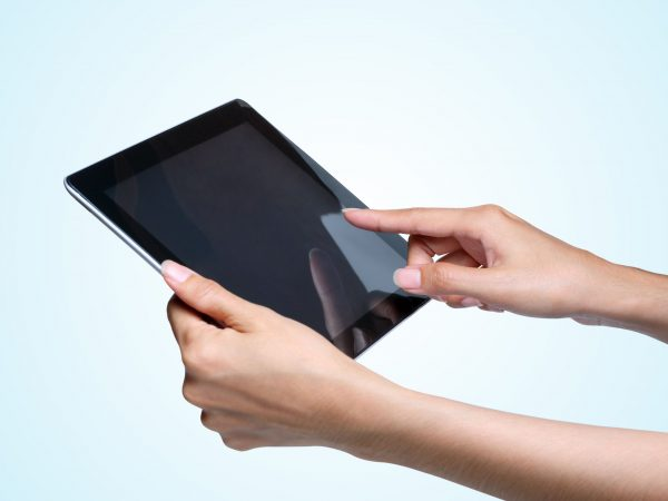 15415164 – female hands holding a tablet pc  on blue background