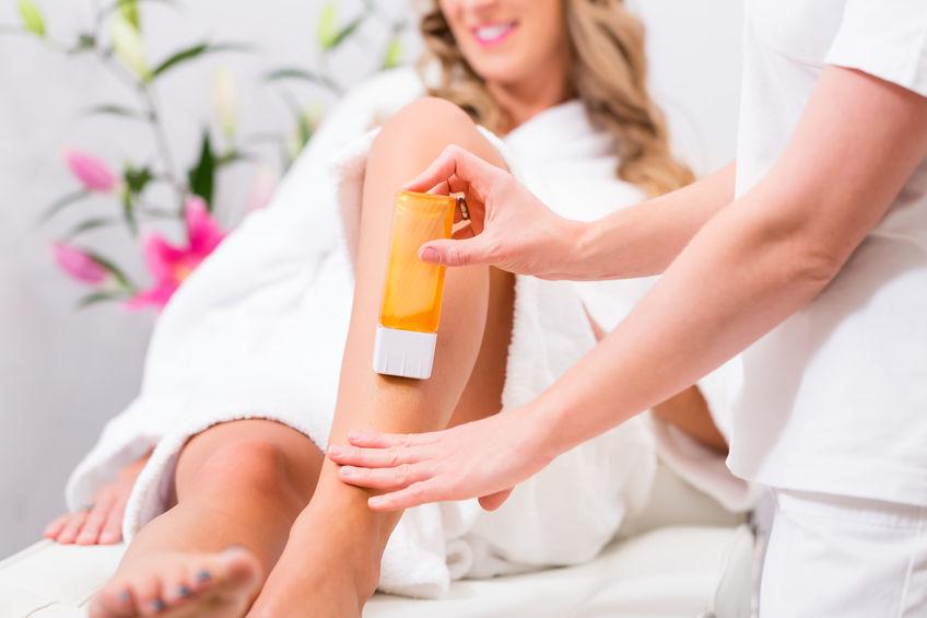Mulher depilando perna com cera roll on.