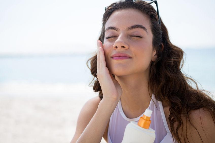 Mulher aplicar protetor solar facial