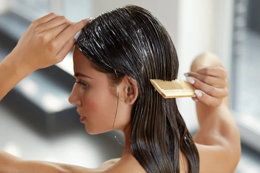 Imagem de mulher passando pente no cabelo com creme.
