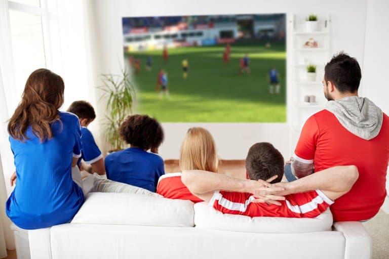 Imagem de amigos assistindo jogo em projeção.