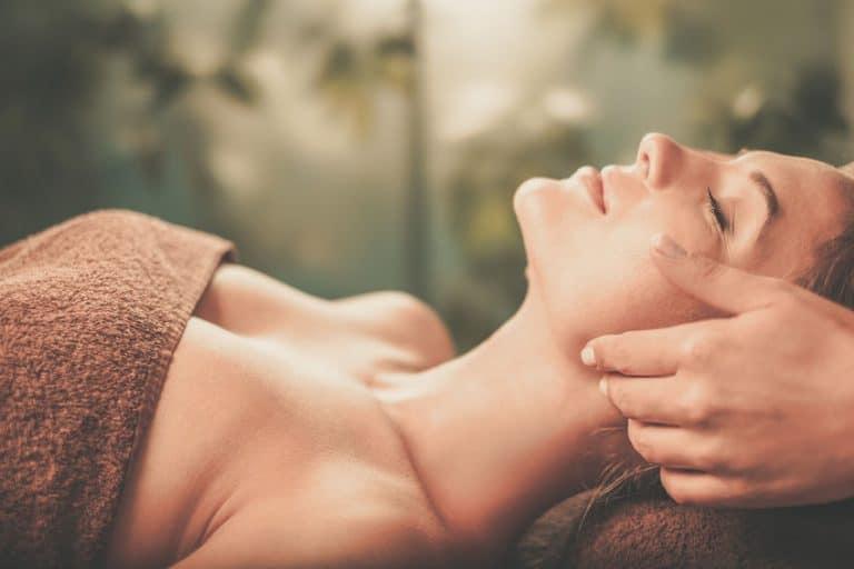 Mulher recebendo massagem no rosto.