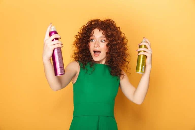 Mulher ruiva segurando shampoo a seco.