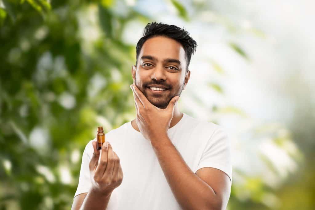 Homem aplicando óleo na barba.