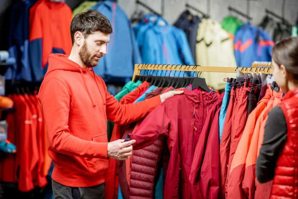Imagem de homem em loja escolhendo corta vento em arara.