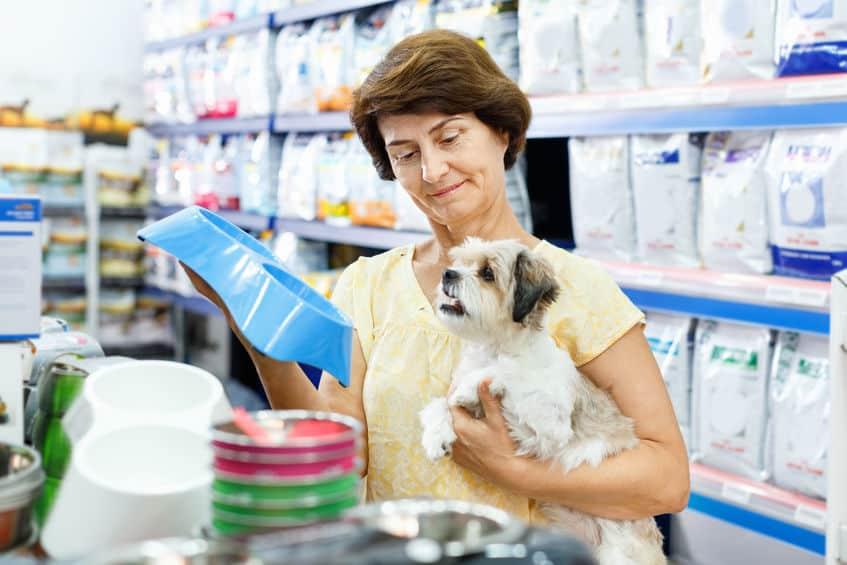 Senhora segurando um filhote de cachorro enquanto escolhe um comedouro