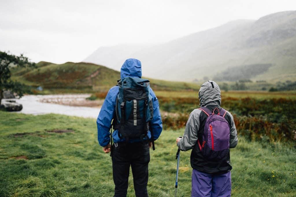 Imagem de duas pessoas caminhando em montanha.