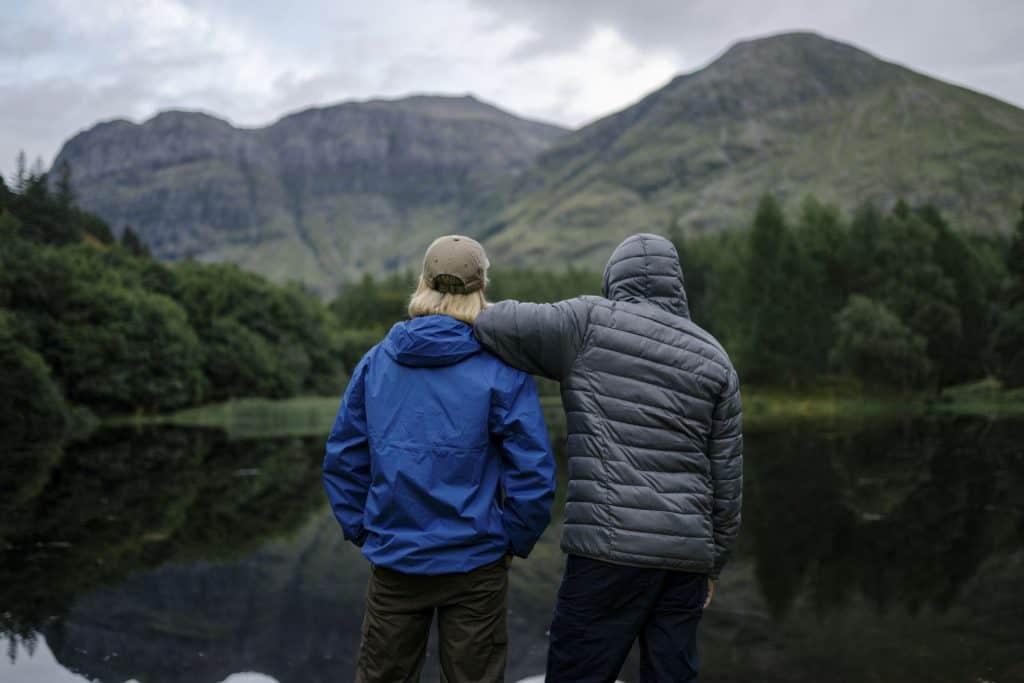 Imagem de casal com jaqueta corta vento em frente a um lago.