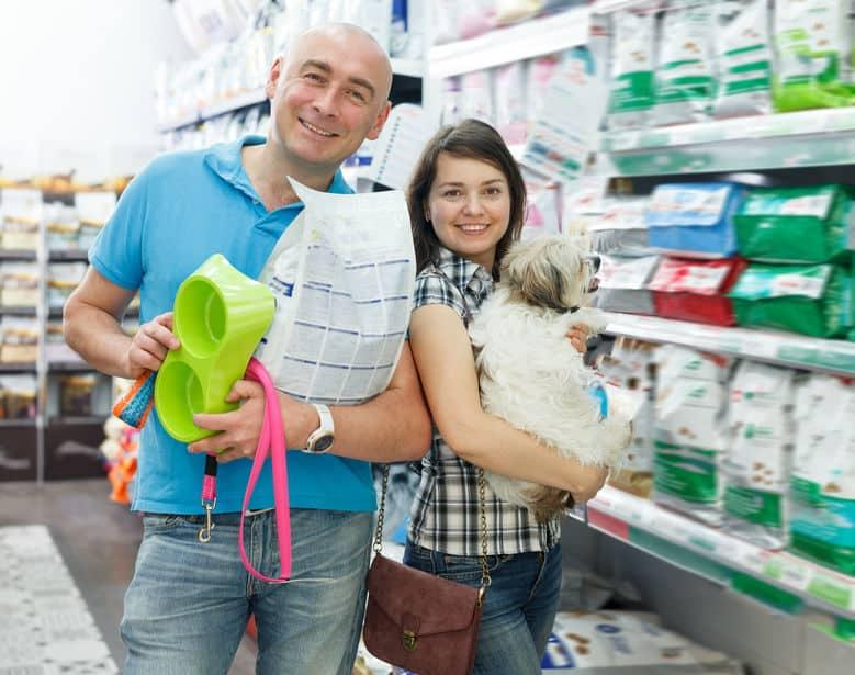 Casal em pet shop comprando ração, coleira e comedouro para seu cachorro
