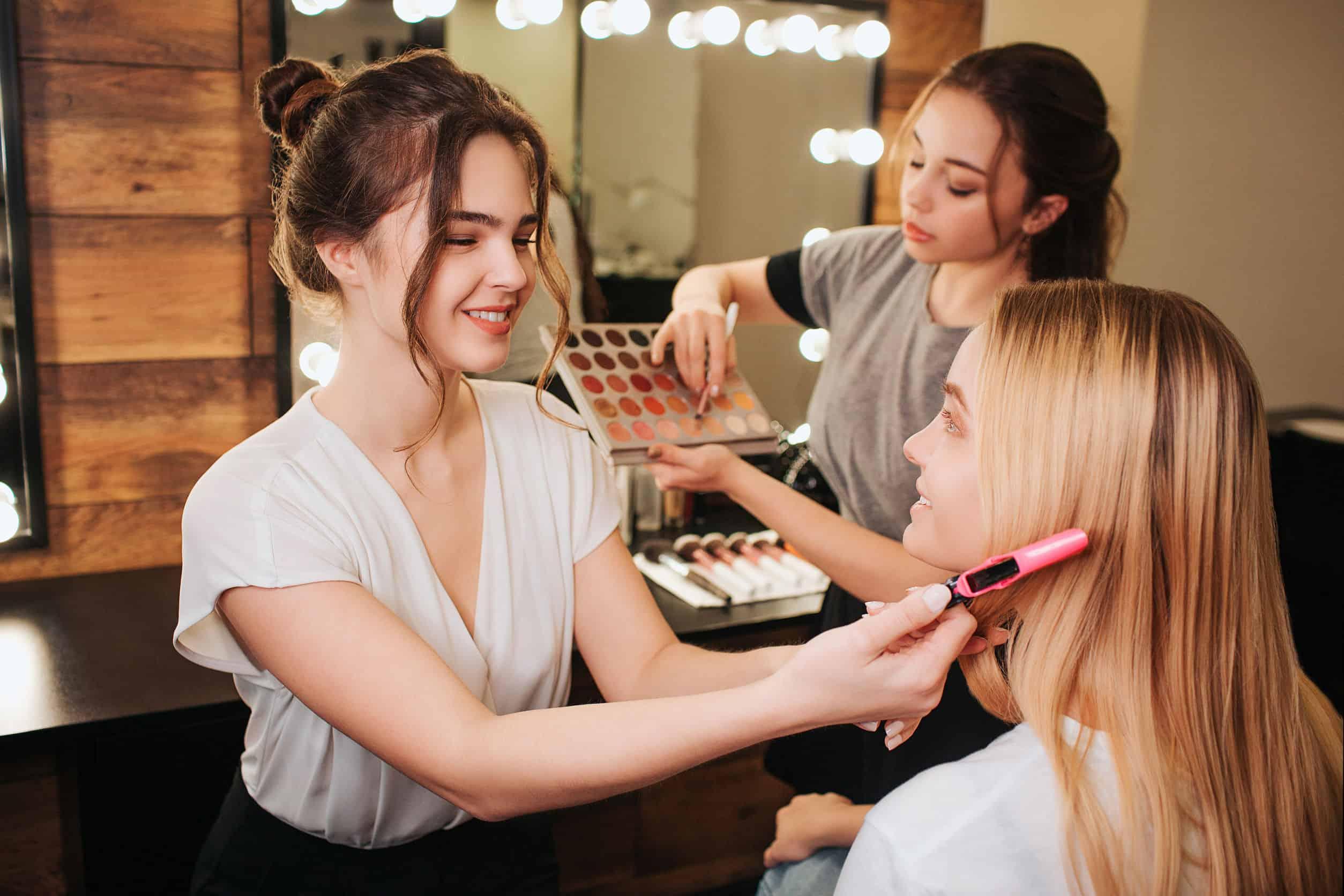Mulher maquiando modelo com maquiagens ao fundo.