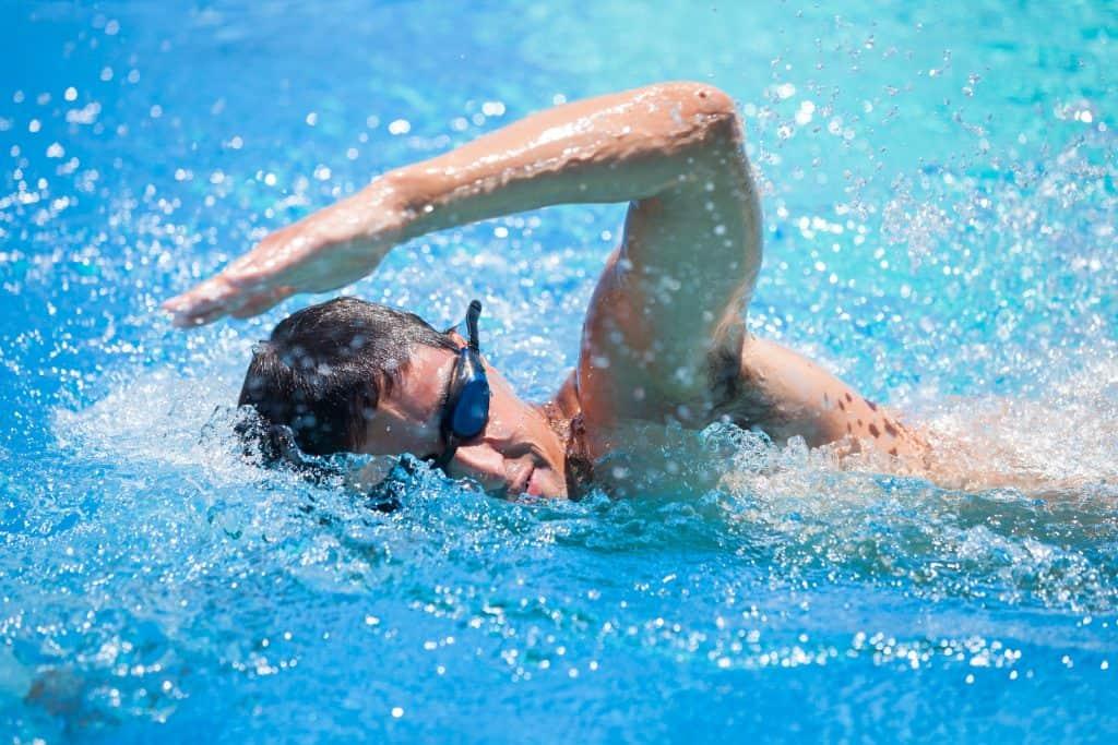 Imagem de homem nadando em piscina e usando óculos de natação.
