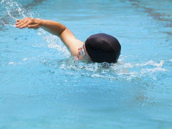 Imagem de pessoa nadando com touca e óculos de natação.