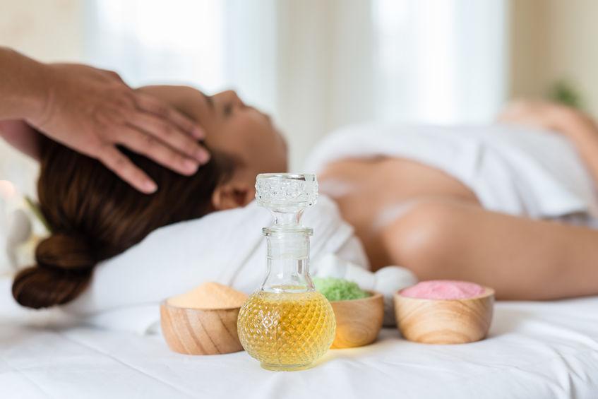 Imagem de um recipiente com óleo, no fundo uma mulher recebendo uma massagem