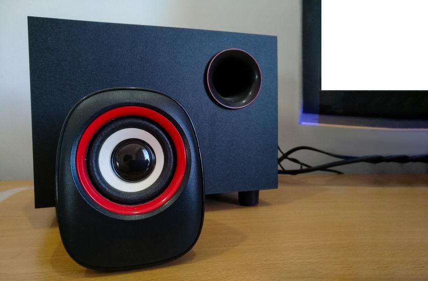 Alto-falante e amplificador de PC na mesa com monitor