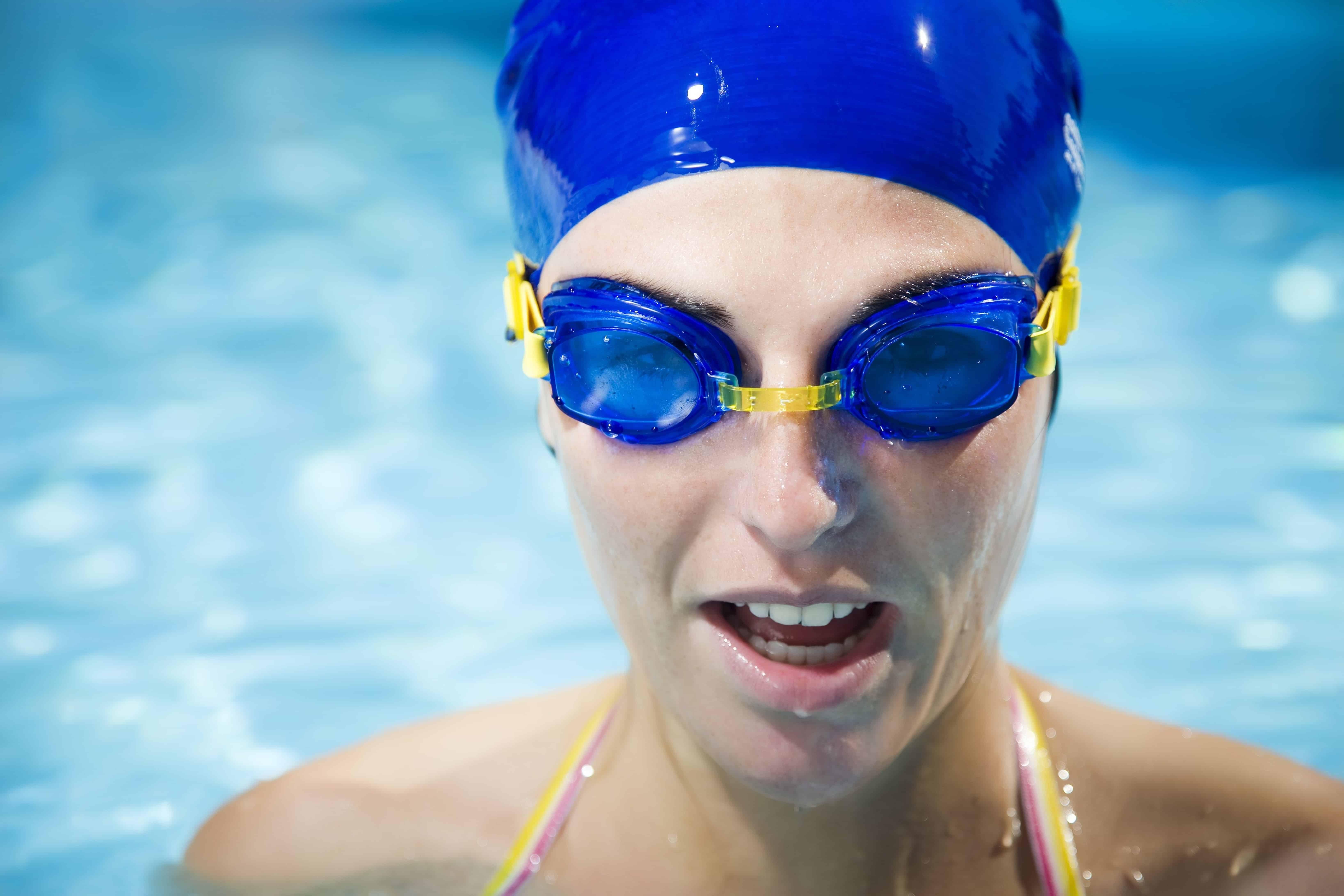 Imagem de pessoa em piscina com óculos de natação.