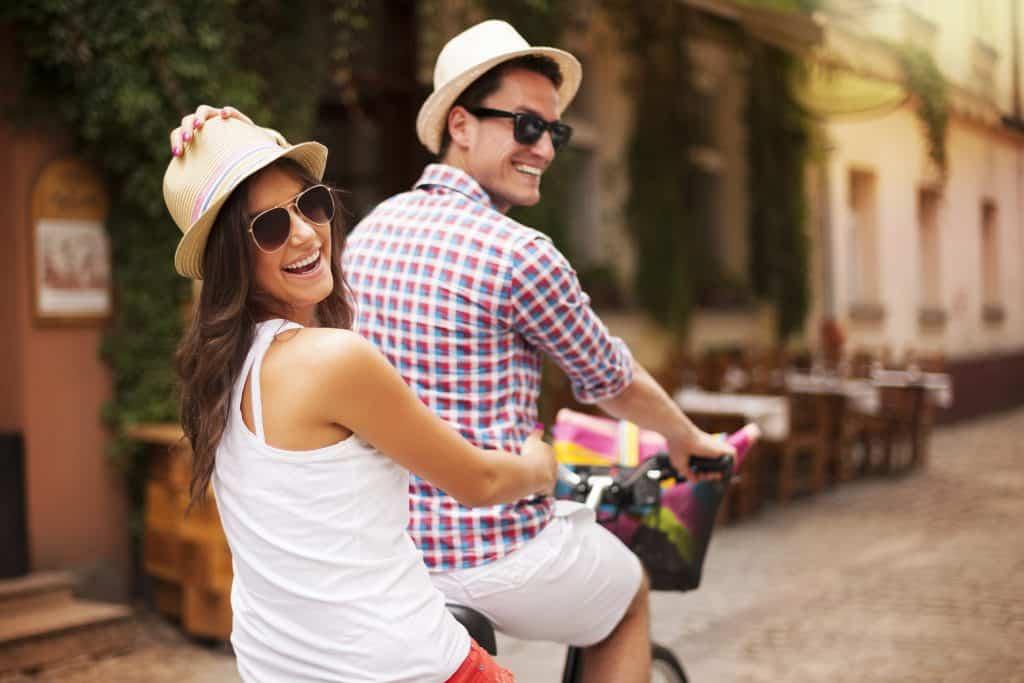 Imagem mostra um casal em uma bicicleta