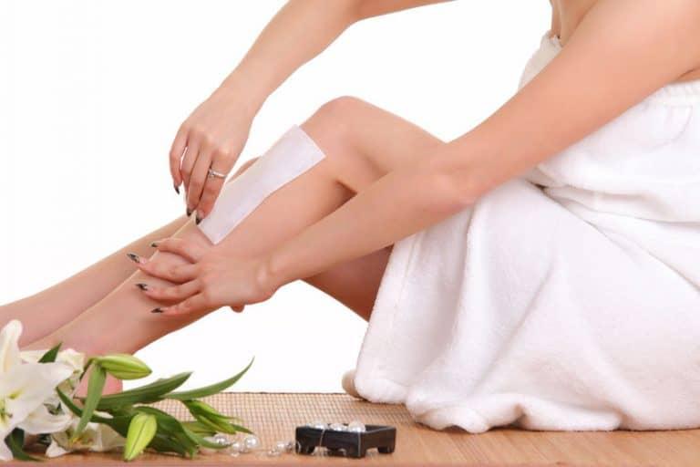 Imagem de mulher depilando pernas.