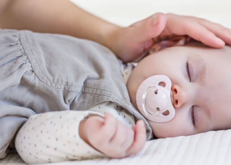 Bebê dormindo com chupeta sendo acariciado pela mãe.