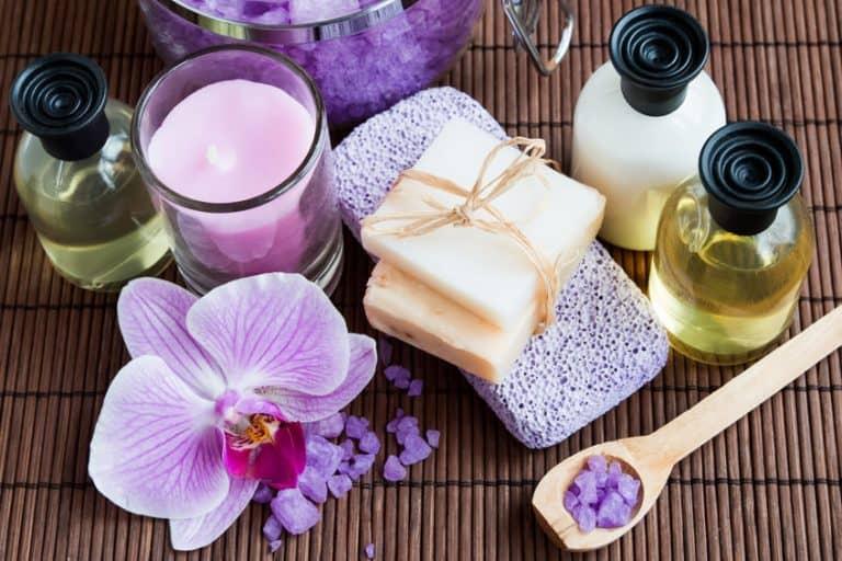 Imagem de sabonete, óleo e sais de banho, com flores.