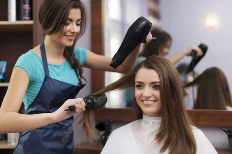 Mulher fazendo escova no cabelo de outra mulher.