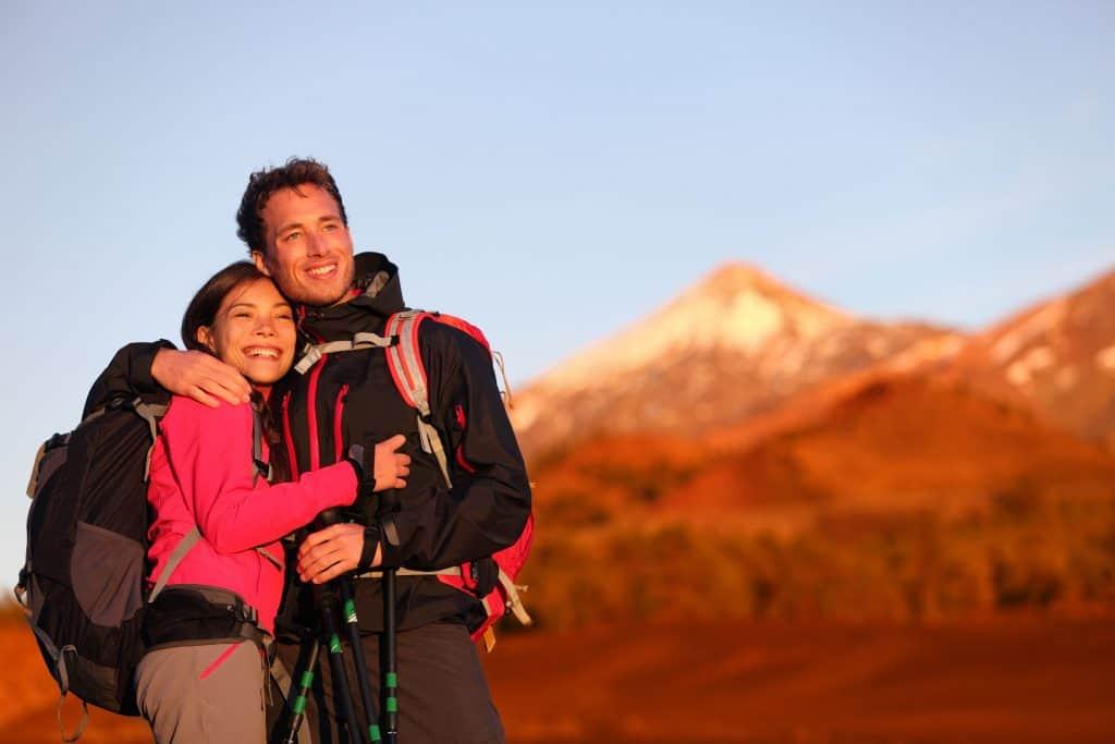 Imagem de casal abraçado com jaqueta corta vento em meio a montanhas.