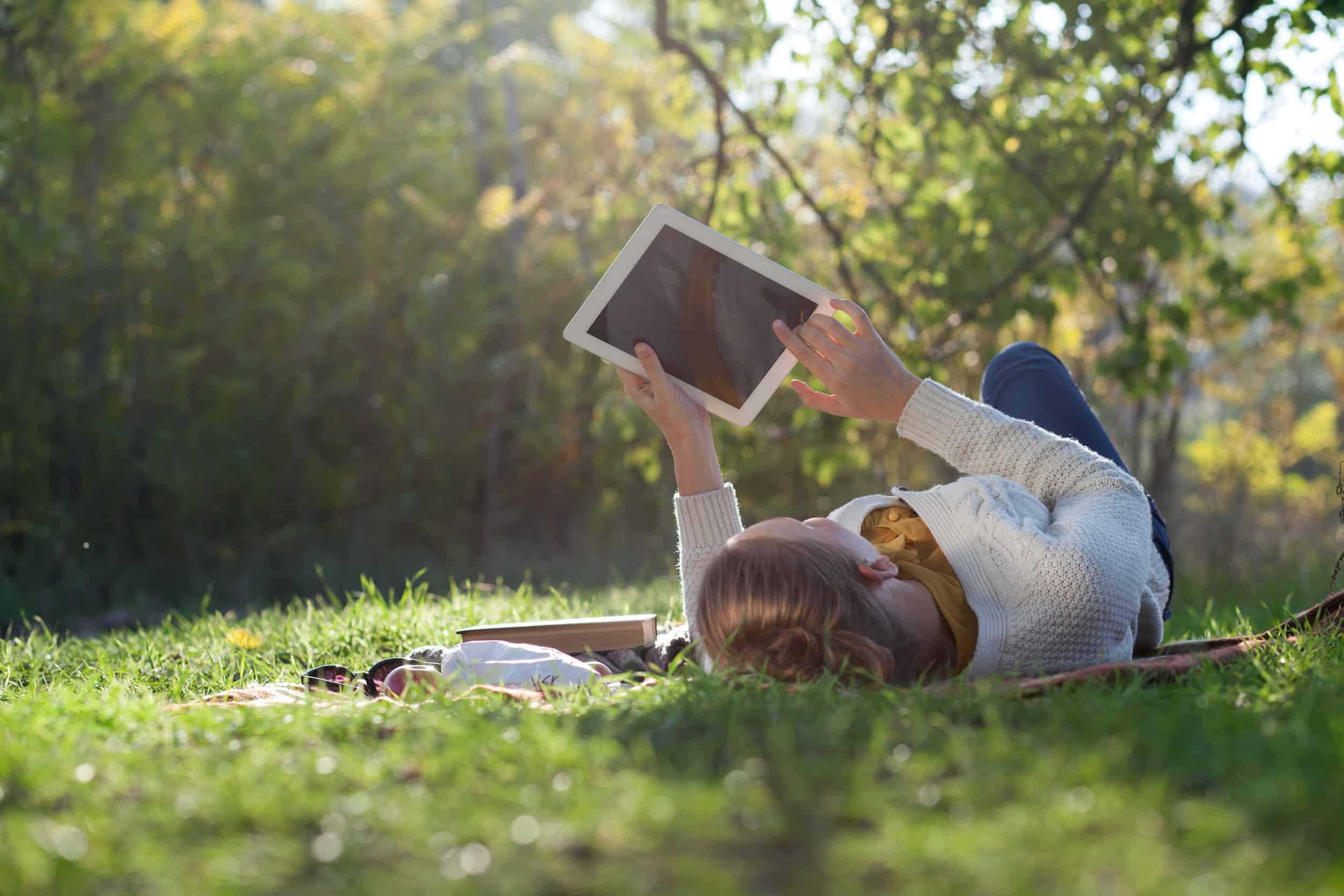 Garota lendo em seu e-reader em parque.