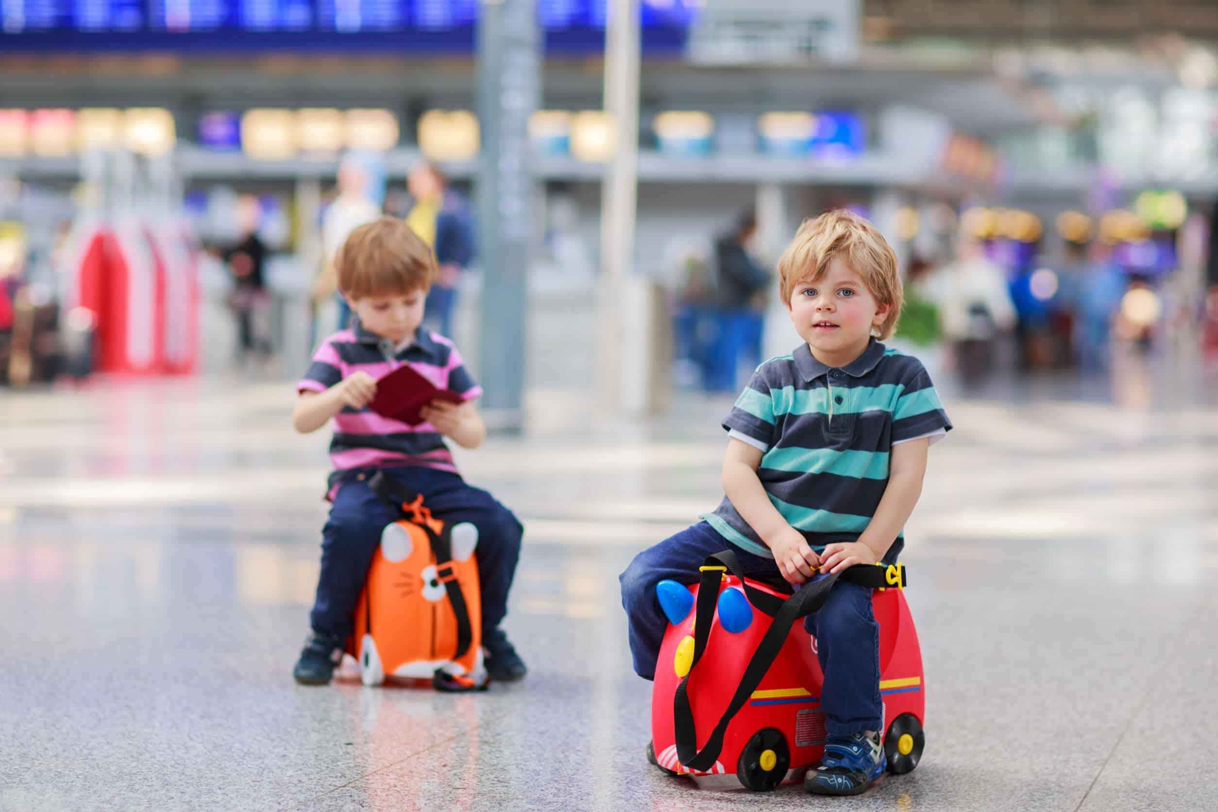 Imagem de meninos sobre mala em aeroporto.