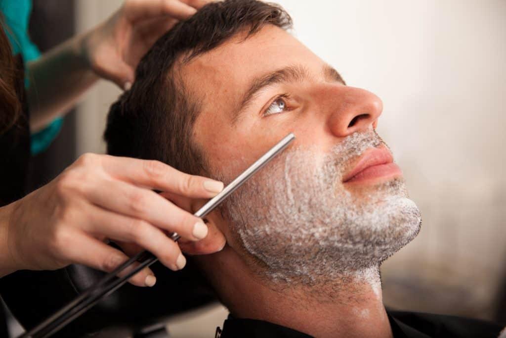 Imagem de homem sendo barbeado com navalha.