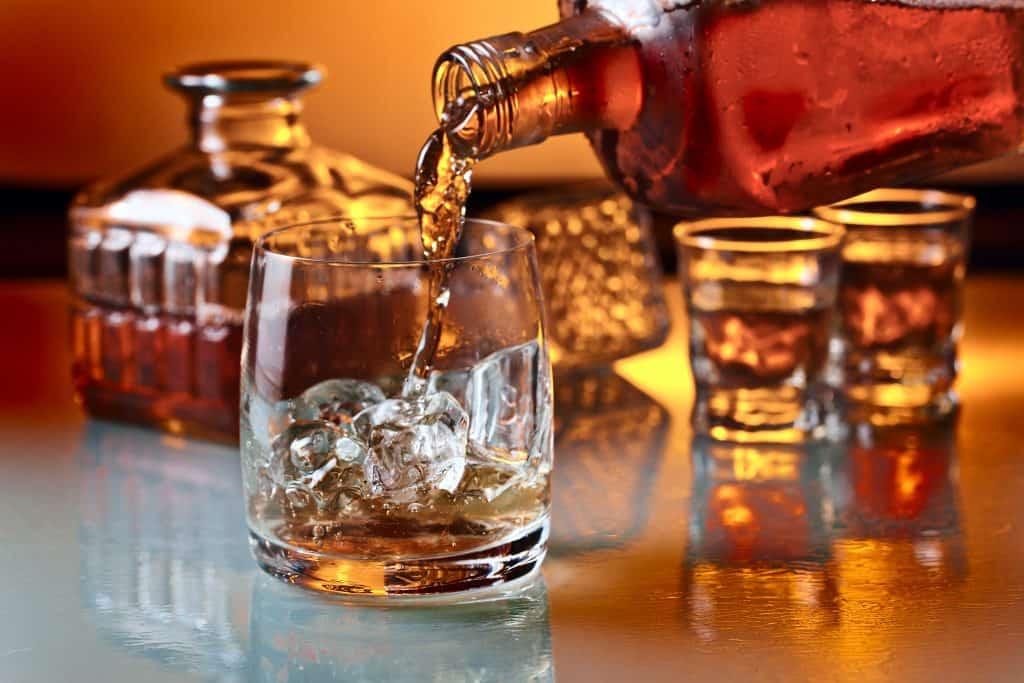 Whisky sendo servido em copo com gelo