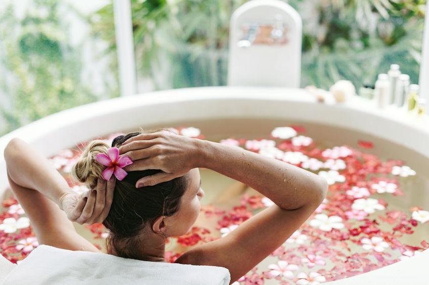 Mulher na banheira com pétalas de rosa