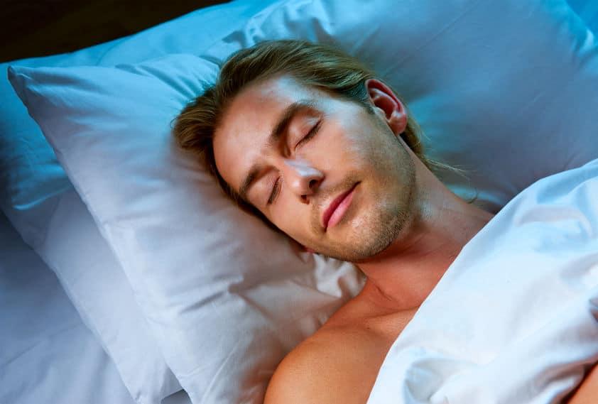 Imagem de homem com cabeça sobre travesseiro dormindo.