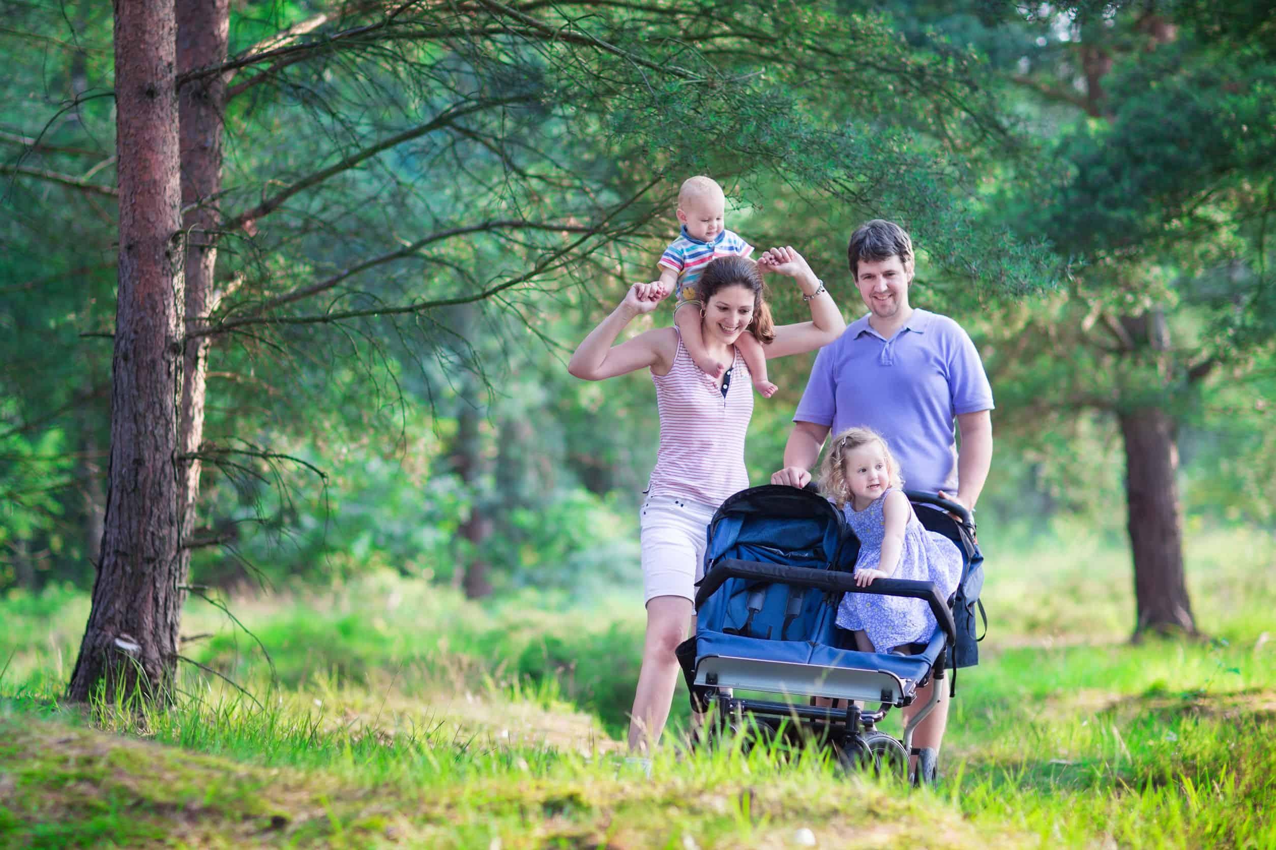 Imagem de pais em natureza com filhos e carrinho para gêmeos.