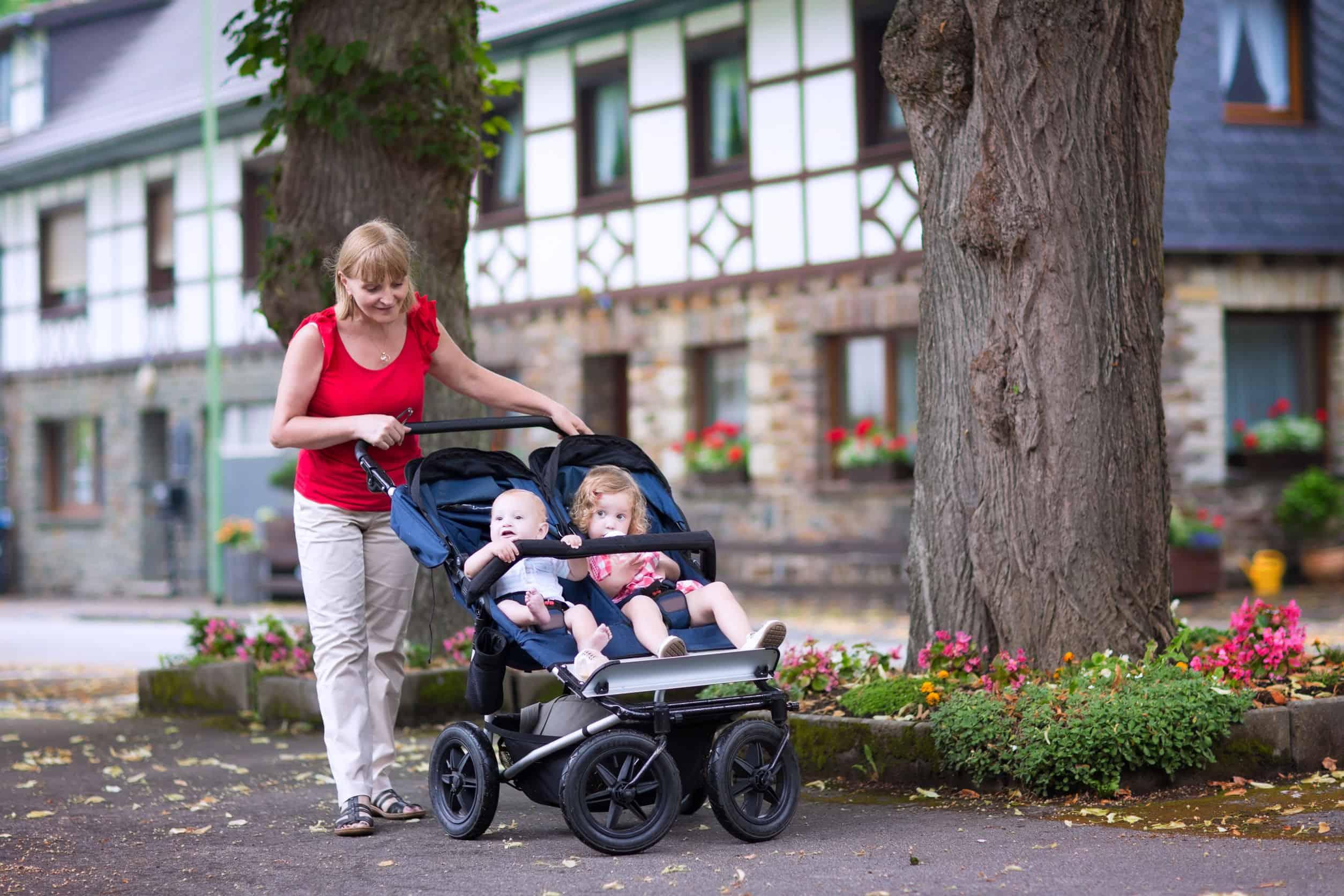 Imagem de mulher empurrando carrinho para gêmeos com duas crianças, de idades diferentes.