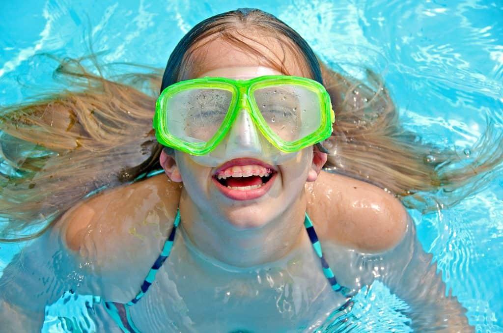 Imagem de criança em piscina usando óculos de natação.