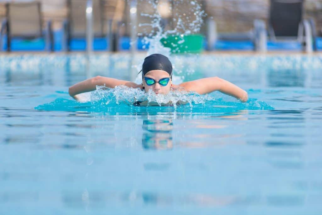 Imagem de pessoa nadando de frente em piscina e usando óculos de natação.