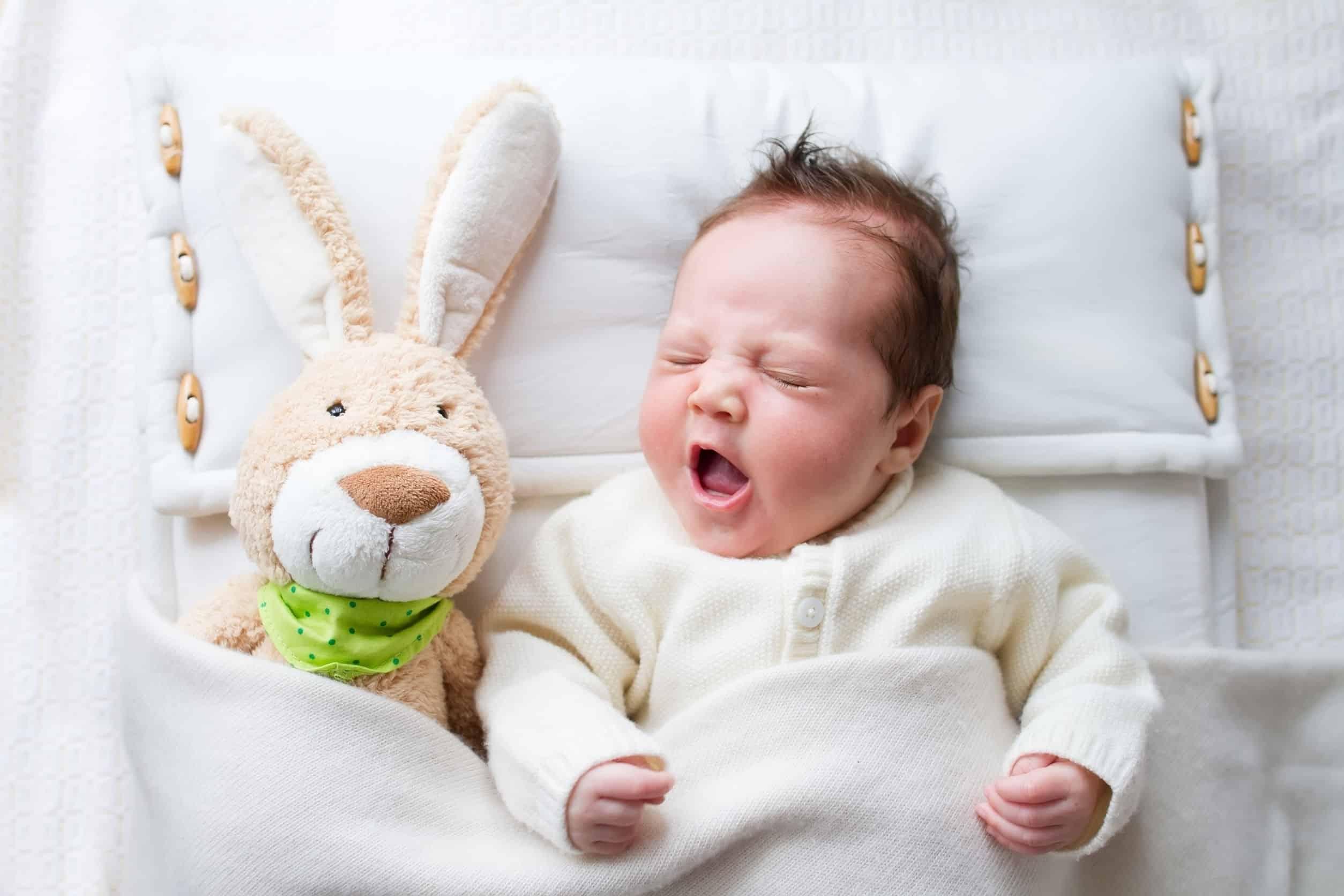 Bebê bocejando dormindo ao lado de coelhinho de pelúcia