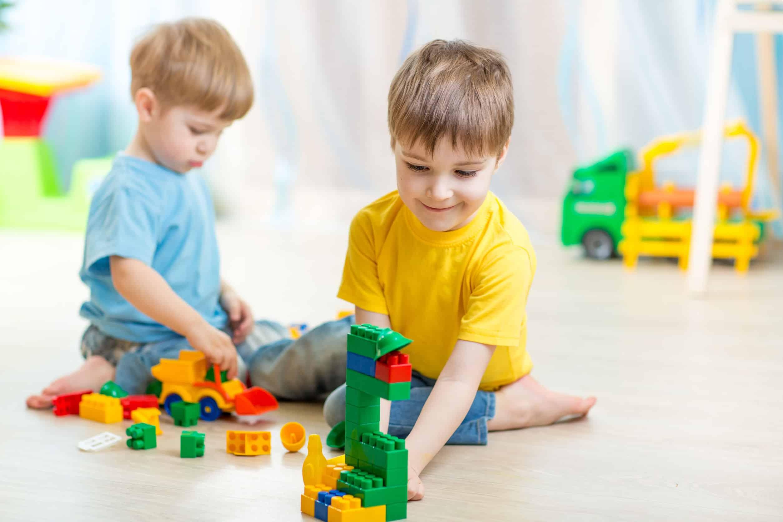 Imagem de dois meninos sentados no chão brincando com lego.