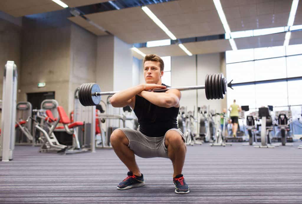 Imagem mostra um homem praticando agachamento em uma academia.