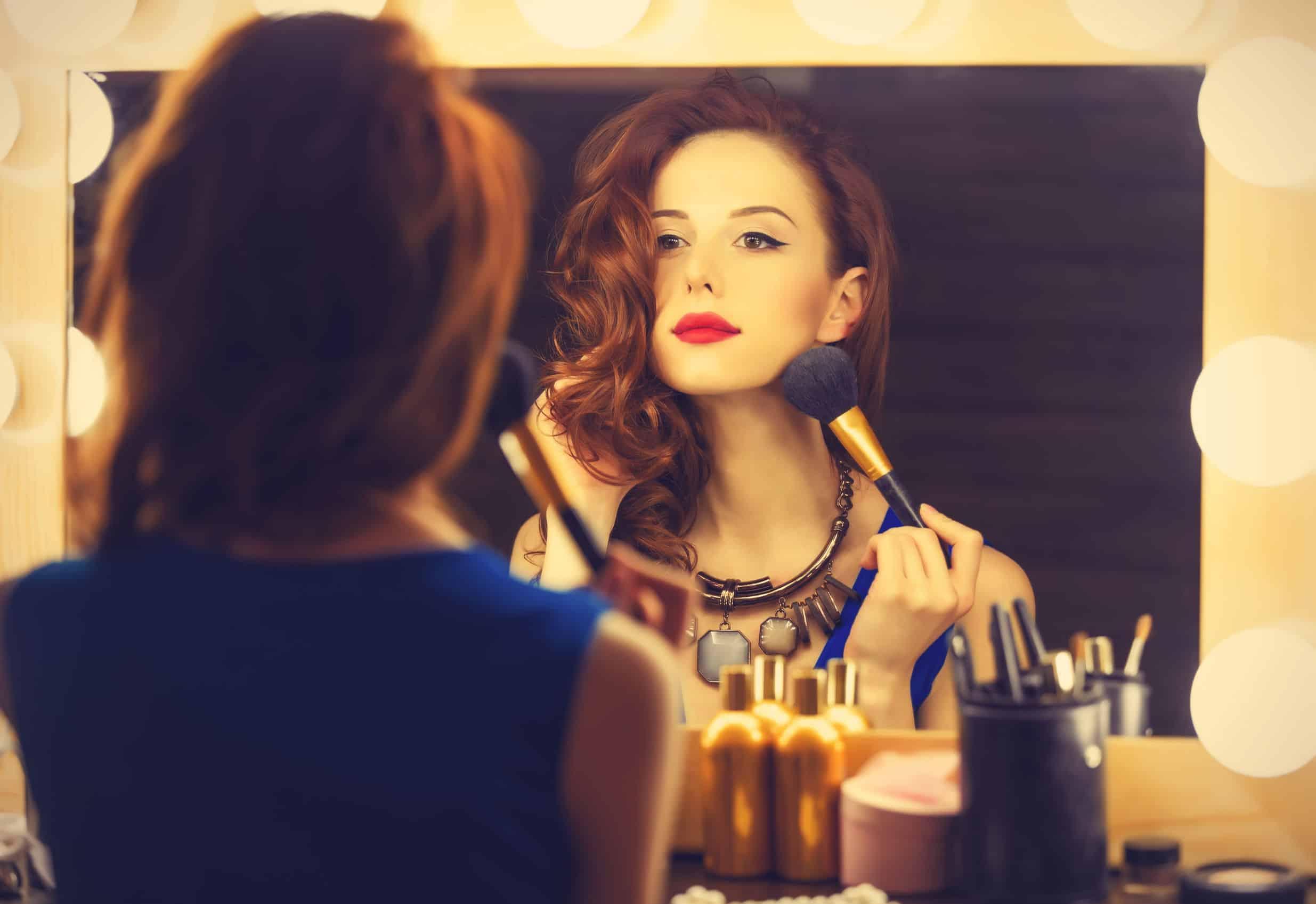 Imagem de mulher se maquiando em frente a espelho.