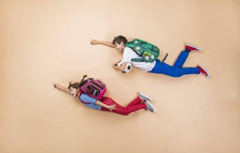Crianças com mochila simulando voo.