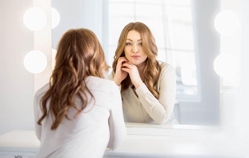 Mulher se olhando em espelho com luzes em volta.