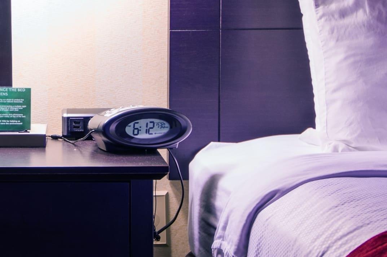 Despertador digital em criado mudo.