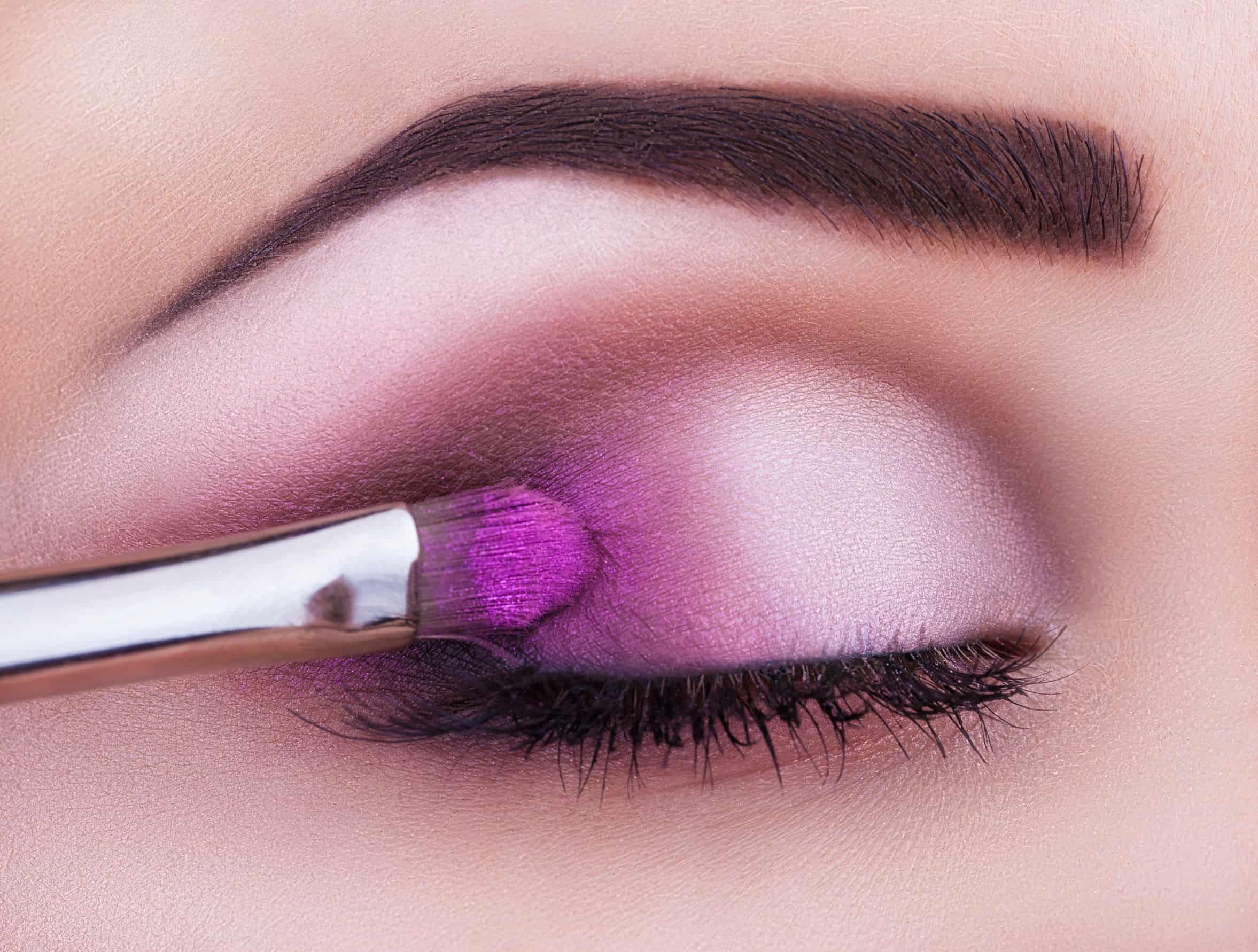 Aplicação de sombra roxa com pincel de maquiagem em closeup