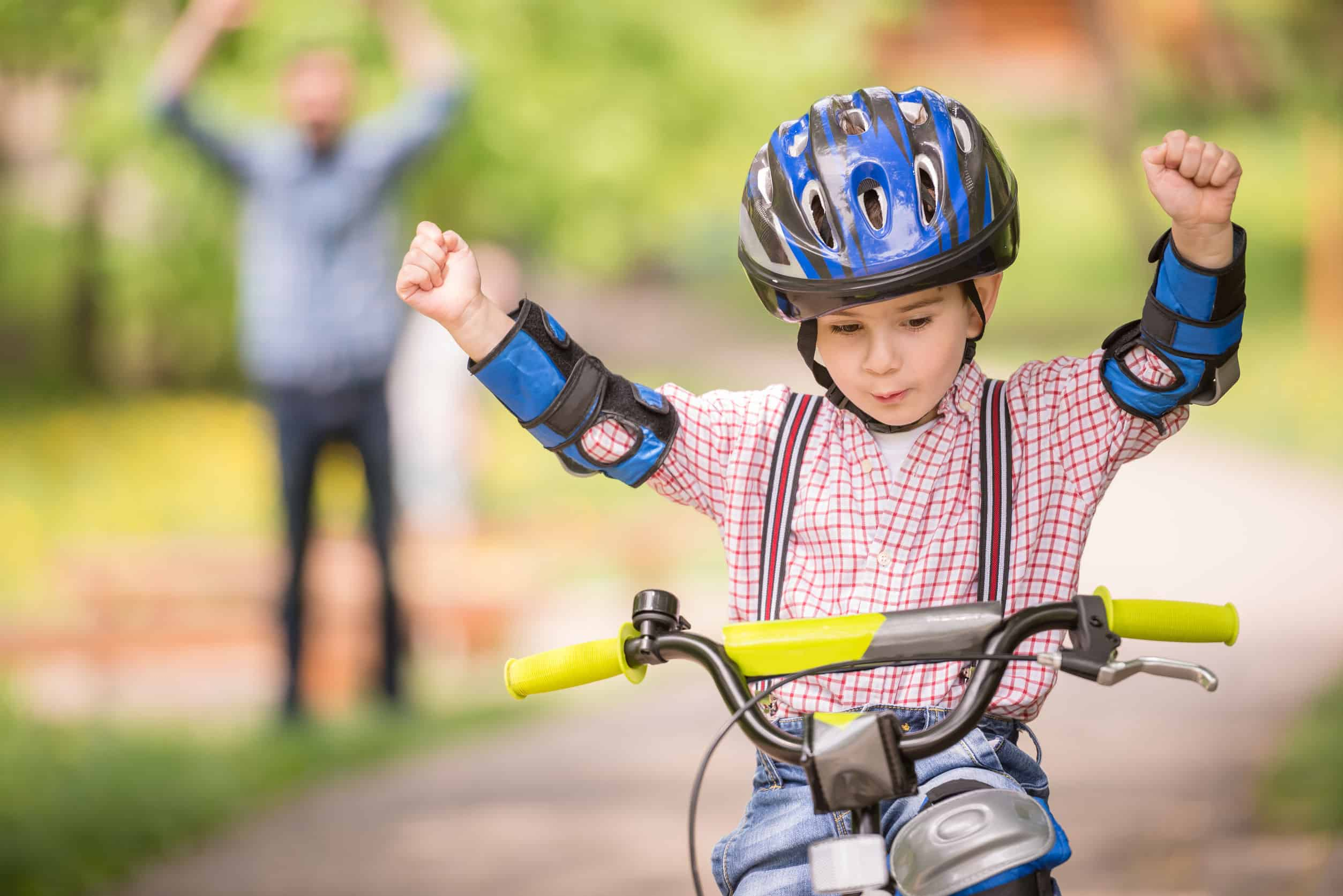 Garoto andando de bicicleta com as mãos levantadas
