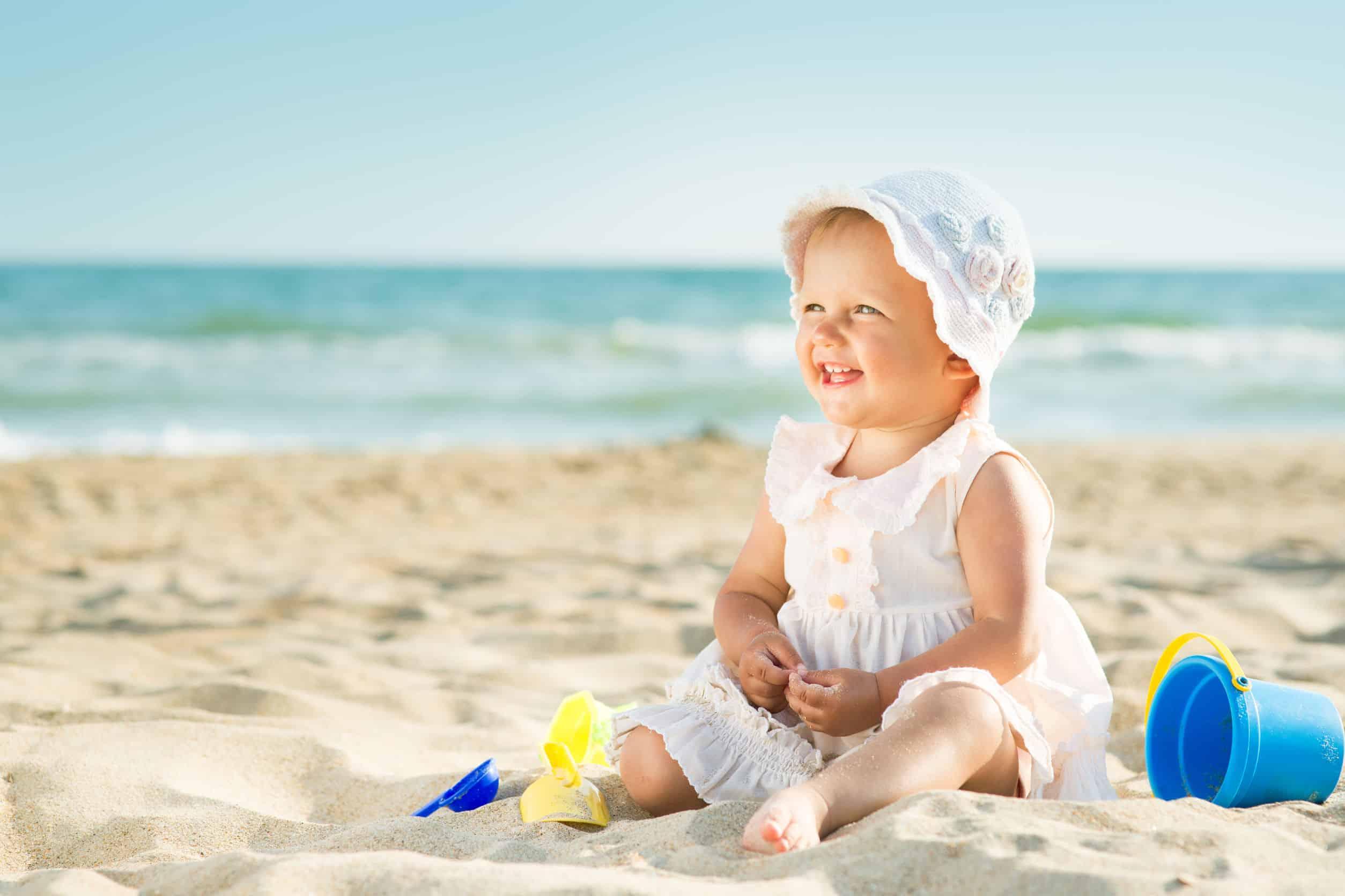 Bebê sentada na praia com brinquedos