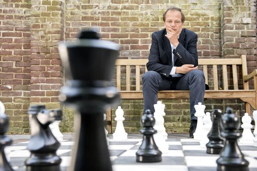 Imagem de homem sentado observando jogo grande de xadrez.