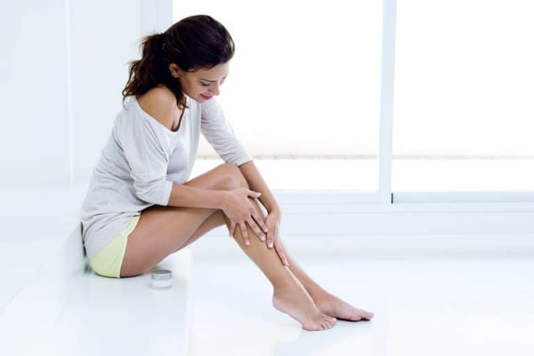 Mulher hidratando perna com óleo.