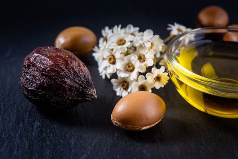 Óleo, sementes e flores sobre mesa.